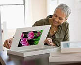 Mixed race woman framing picture of flowers