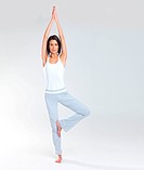 Exercise_ Beautiful brunette woman in yoga stance in workout clothes stretching up