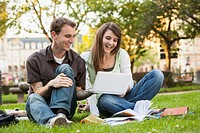 Caucasian students sitting in grass looking at laptop