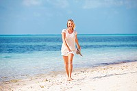Full length of beautiful mature woman taking stroll on beach