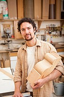 Mixed race man woodworking in workshop