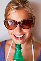 Closeup portrait of gorgeous young lady sipping soft drink