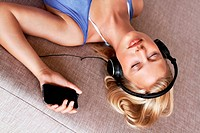 Casual woman lying on sofa listening to music from her mobile phone