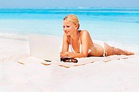 Full length of young woman in bikini with laptop relaxing at beach
