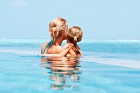 Mother and her daughter looking out at the ocean from their pool