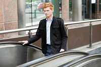 Businessman standing on escalator moving up
