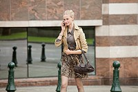 Businesswoman crossing the road while talking on a mobile phone (thumbnail)