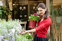 Woman holding a potted plant and looking at flowers in a flower shop