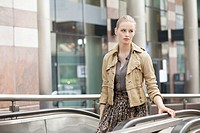 Businesswoman standing on escalator (thumbnail)