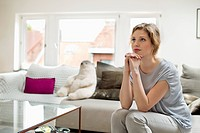 Woman sitting on a couch and looking away (thumbnail)