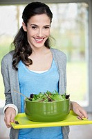 Woman carrying a bowl of salad on a tray (thumbnail)