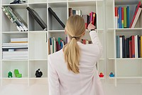 Woman taking out a book from shelf (thumbnail)