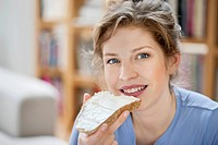 Portrait of a woman eating toast with cream spread on it (thumbnail)