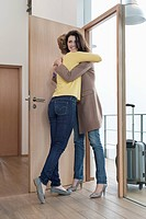 Woman welcoming her friend at doorway (thumbnail)