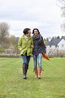 Two women walking in a lawn