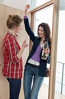 Woman arriving at her friends home with a wine bottle (thumbnail)
