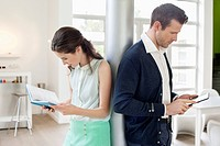 Man using an electronic book with a woman reading a book