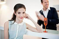 Woman smiling with her husband shaking cocktail in the background (thumbnail)