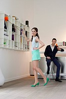 Woman cleaning a bookshelf and her husband drinking champagne in the background