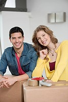 Couple leaning over cardboard boxes and smiling
