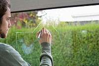 Man drawing an architecture design on the glass of window (thumbnail)