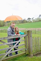 Man standing with his daughter in a farm with an umbrella (thumbnail)
