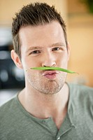 Man making artificial mustache with green bean