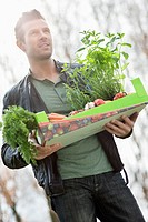 Man holding a tray of raw vegetables