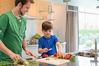Man looking at his son cutting vegetables in the kitchen