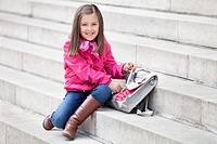 Portrait of a girl opening her schoolbag and smiling