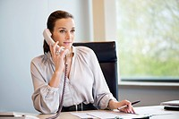 Businesswoman talking on a landline phone in an office