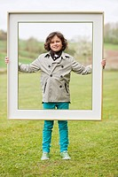 Portrait of a boy standing with a frame in a park