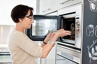 Elderly woman putting a tray into an oven