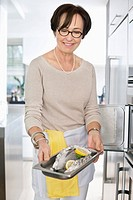 Elderly woman showing a tray of seafood in front of an oven