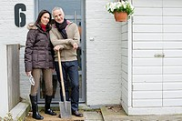 Couple standing at the doorway with a shovel (thumbnail)