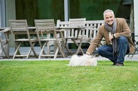 Man playing with his pets in a garden (thumbnail)