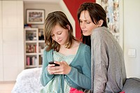 Girl text messaging on mobile phone with her mother at home