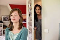 Woman watching her daughter behind the door in the bedroom