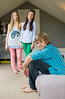 Teenage boy with his two sisters smiling at home