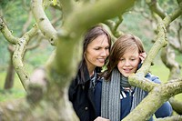 Woman with her daughter looking at a tree branch in an orchard (thumbnail)