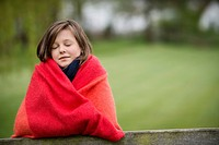 Girl wrapped in a blanket with her eyes closed in a farm (thumbnail)