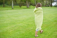Girl wrapped in a blanket and walking in a field (thumbnail)