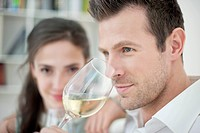 Man drinking white wine with his wife in the background