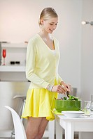 Woman mixing salad at a dining table