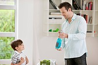 Man showing sparkling water bottle to his son