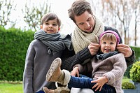 Man with his son and daughter in warm clothing in a park