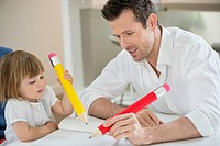 Man and daughter writing with big pencils