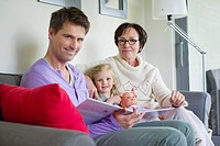 Girl studying with her father and grandmother at home (thumbnail)