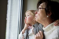 Woman with her granddaughter looking through a window