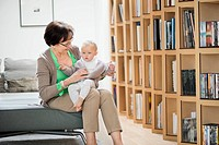 Woman sitting on a couch playing with her granddaughter